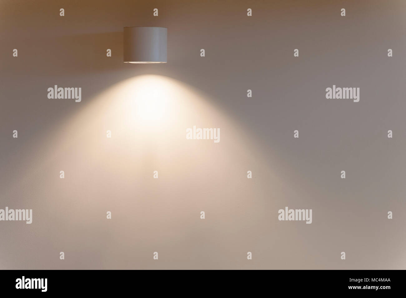 A directional light fixture on a wall casts a soft light on a bare wall. - Stock Image