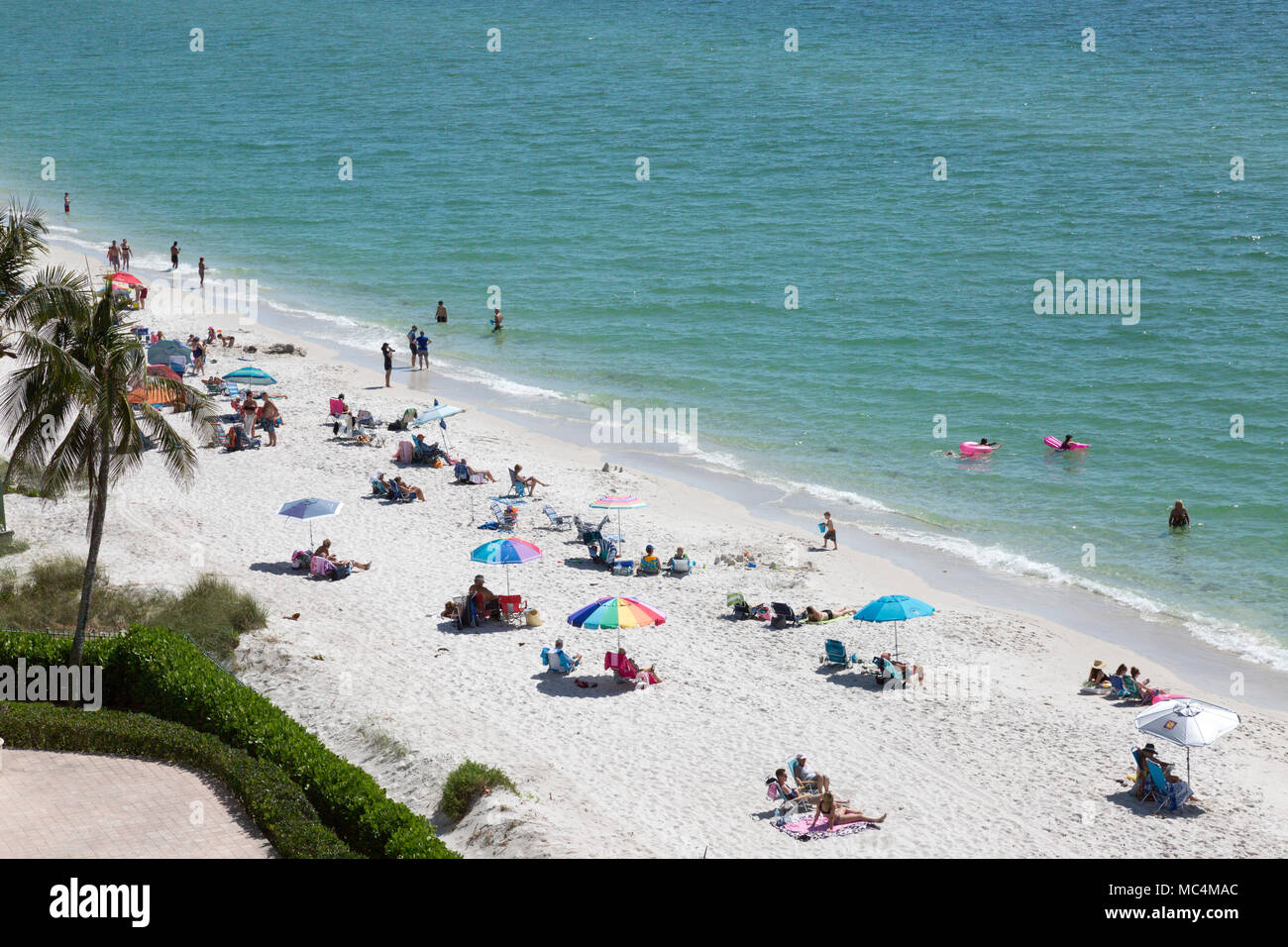 View from above of beach scene along the coast of Florida in Naples. Families vacationing over spring break. Colorful beach umbrellas. - Stock Image