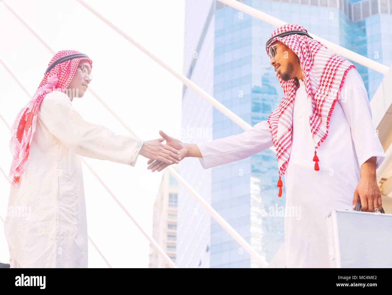 Arab and business man are shaking hand on cityscape background - Stock Image
