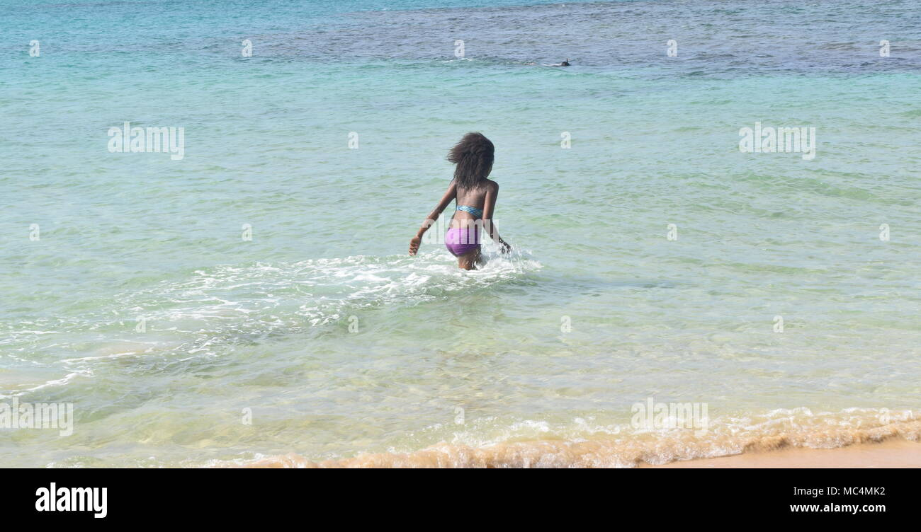 Girl running into the sea on a sunny day - Stock Image