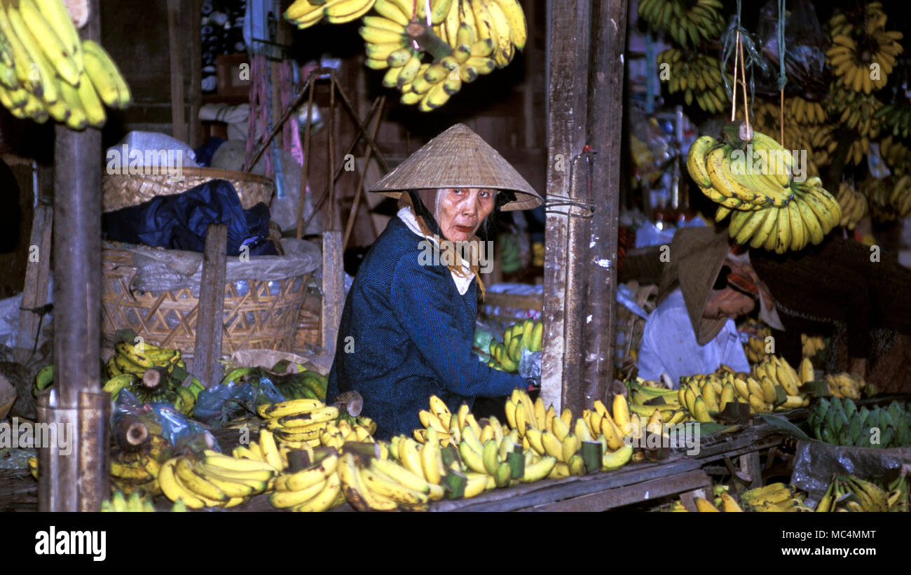 A woman in a traditional straw hat selling bananas at a local market in Vietnam.Stock Photo