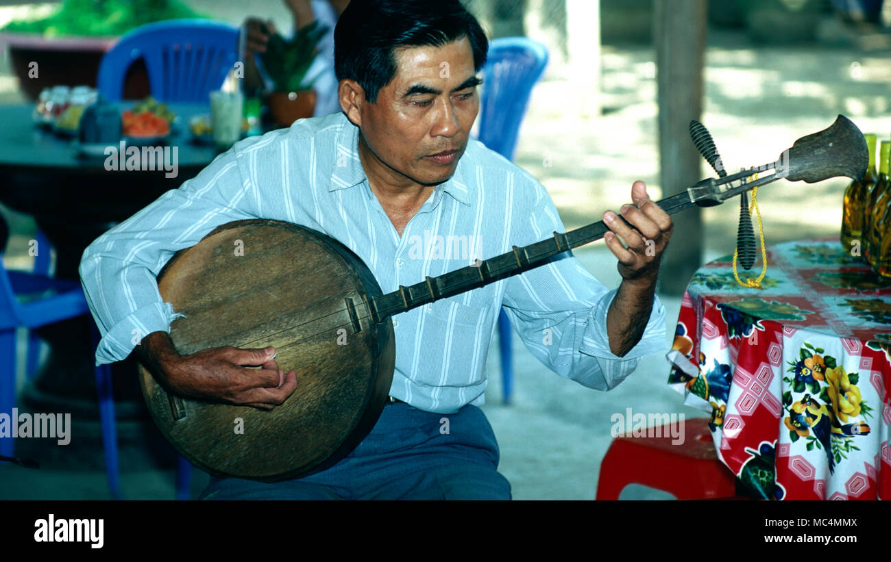 A Vietnamese man playing a traditional two-stringed guitar. - Stock Image