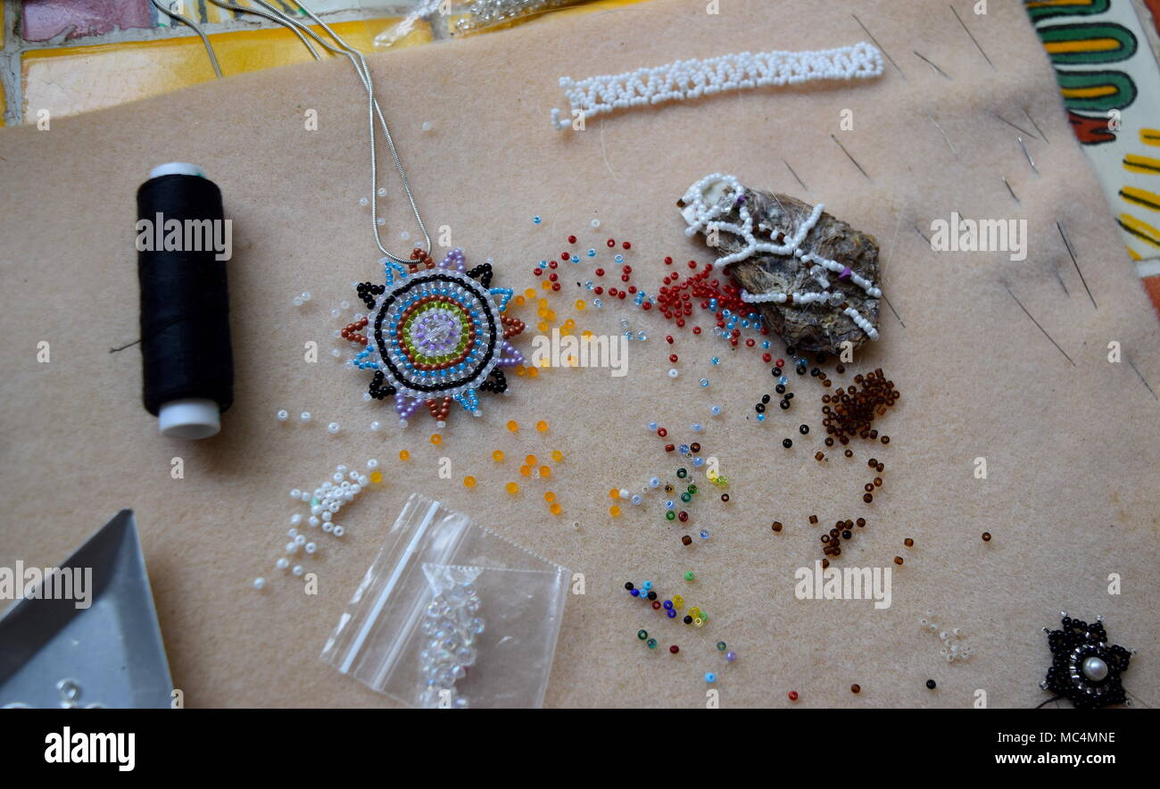 Beading mat with finished designs, needles and colourful beads - Stock Image