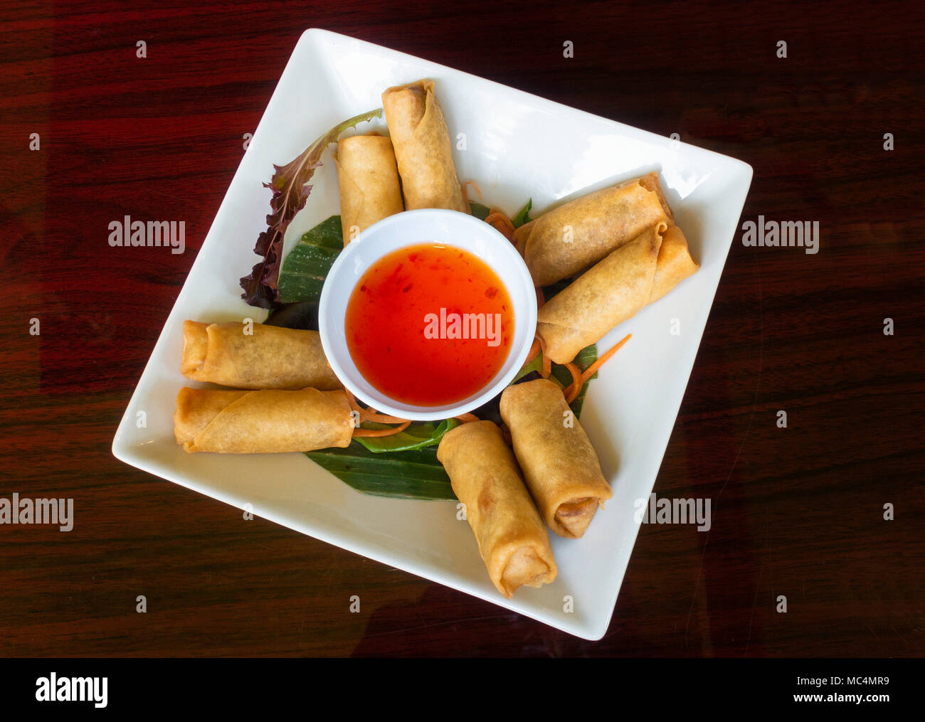 Thai spring rolls with a spicy dipping sauce - Stock Image