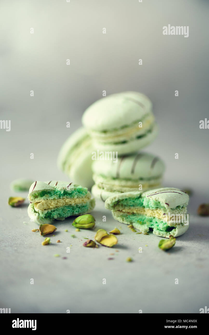 Green mint french macaroons with pistachios. Pastel colors macarons, copy space. Holidays and celebrations concept. Sweet gift for woman, girl - Stock Image