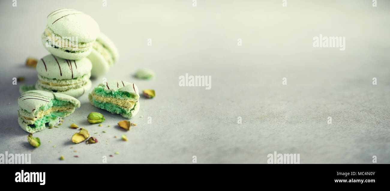 Green mint french macaroons with pistachios. Pastel colors macarons, copy space. Holidays and celebrations concept. Sweet gift for woman, girl. Banner - Stock Image