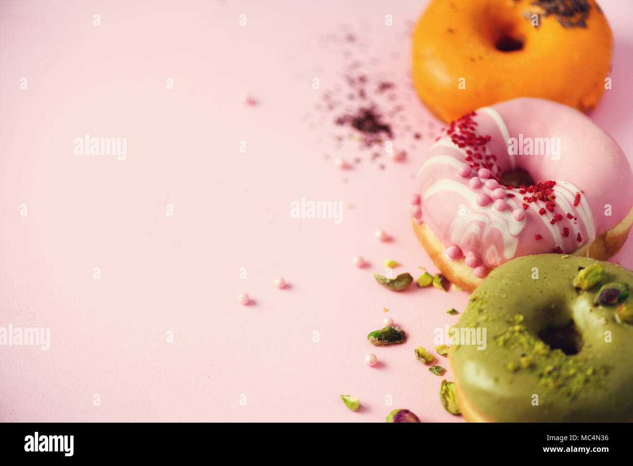 Colorful donuts with icing on pastel pink background. Sweet orange, green, pink doughnuts with pistachio, chocolate. Flat lay, top view, copy space - Stock Image