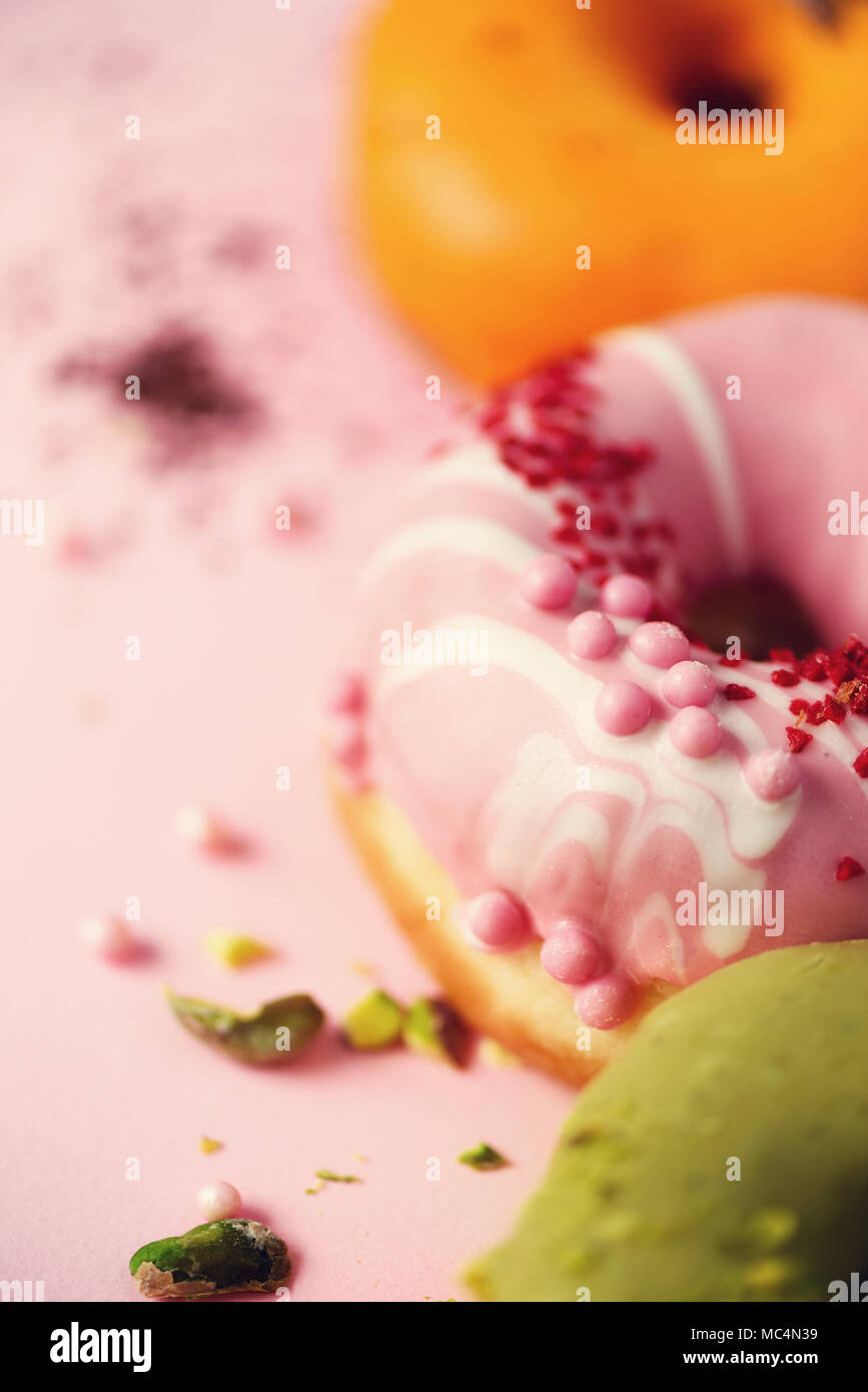 Colorful donuts with icing on pastel pink background. Sweet orange, green, pink doughnuts with pistachio, chocolate. Flat lay, top view, copy space Stock Photo