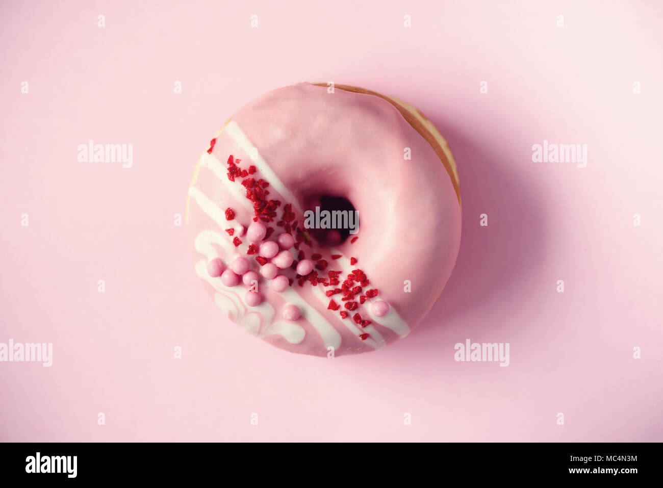 Sweet doughnut with pink icing on pastel background. Tasty donut on pink texture, copy space, top view - Stock Image