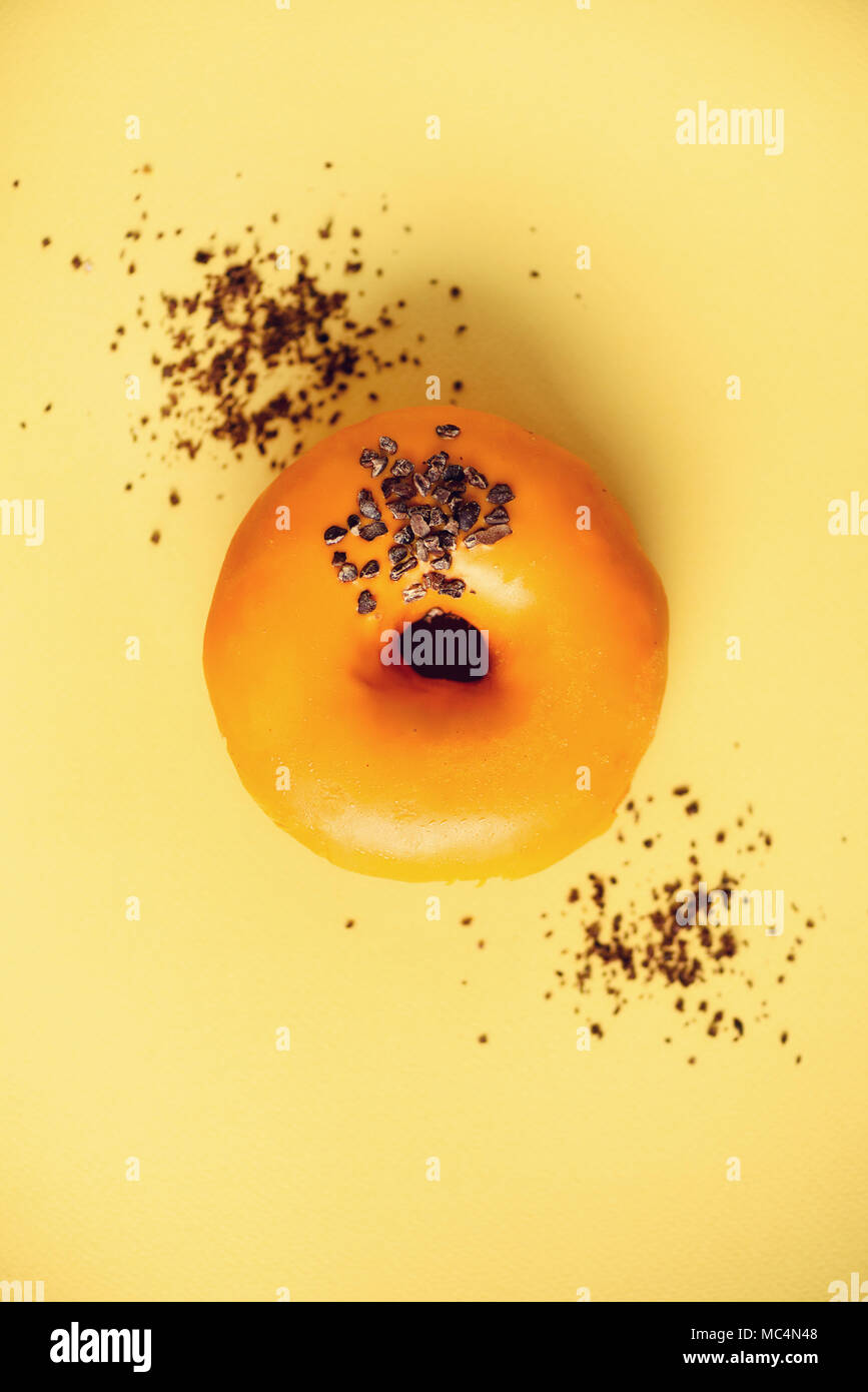 Sweet doughnut with orange glaze and chocolate on grey background. Tasty donut on pastel yellow texture, copy space, top view - Stock Image