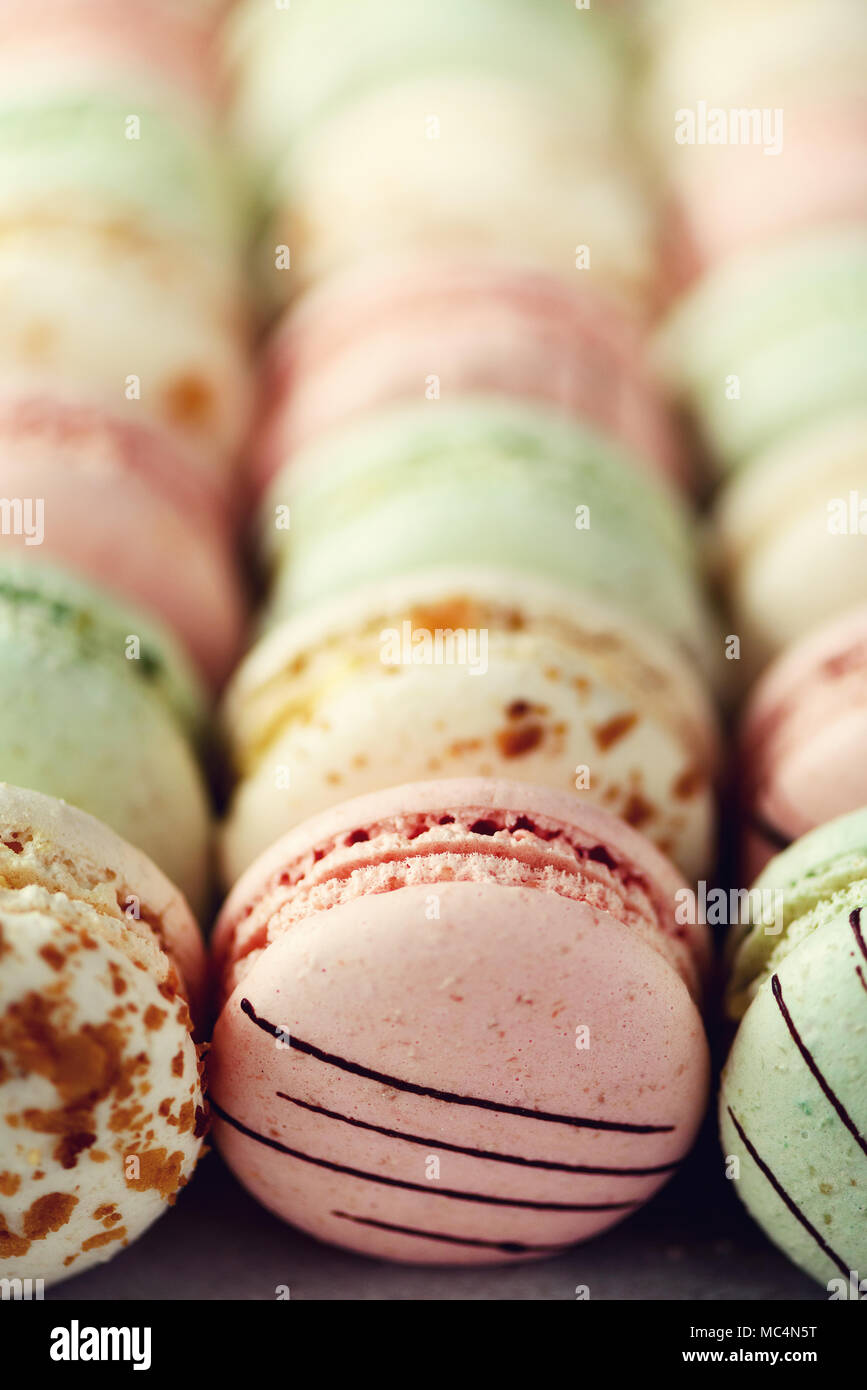 Colorful french macaroons flat lay. Pastel colors pink, green, yellow macarons with copy space, top view. Holidays and celebrations concept. Sweet gift for woman, girl Stock Photo