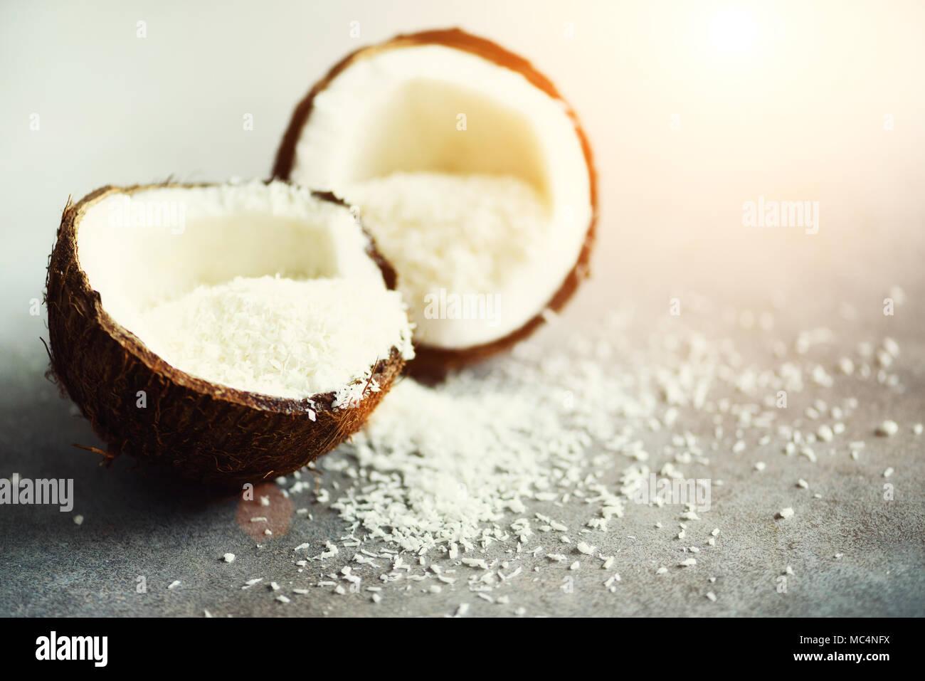 Coconut fuit halves with coconut shavings on grey concrete background. Copyspace - Stock Image