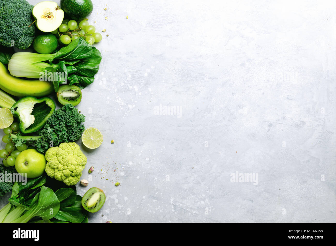 Organic green vegetables and fruits on grey background. Copy space, flat lay, top view. Green apple, lettuce, zucchini, cucumber, avocado, kale, lime, kiwi, grapes, banana, broccoli - Stock Image