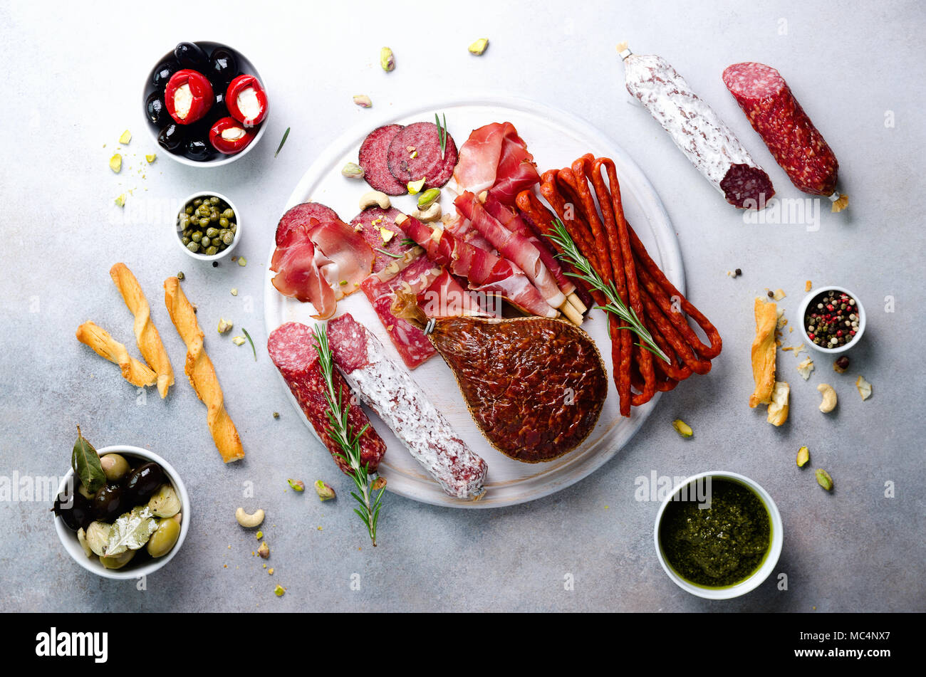 Traditional italian antipasto, cutting board with salami, cold smoked meat, prosciutto, ham, cheese, olives, capers on grey background. Cheese and meat appetizer. Top view, copy space, flat lay - Stock Image