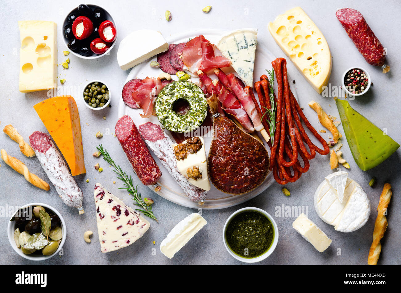 Traditional italian antipasto, cutting board with salami, cold smoked meat, prosciutto, ham, cheeses, olives, capers on grey background. Cheese and meat appetizer. Top view, copy space, flat lay - Stock Image