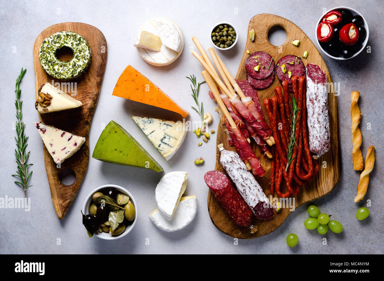 Cutting board with cold smoked meat, prosciutto, salami, assortment of cheeses, bread sticks, capers, olives on grey stone background. Cheese and meat appetizer. Top view, copy space, flat lay Stock Photo