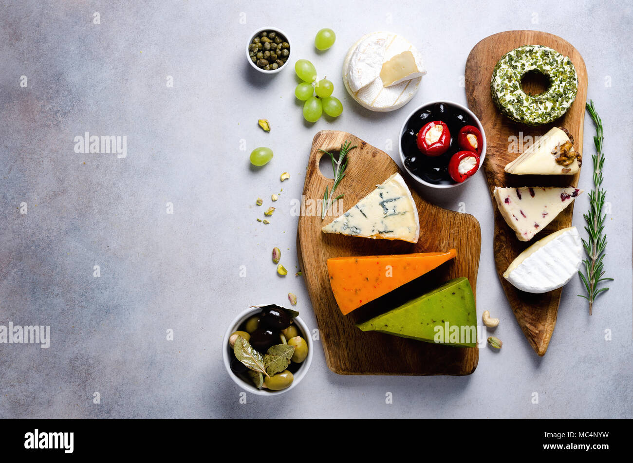 Assortment of hard, semi-soft and soft cheeses with olives, grissini bread sticks, capers, grape, on grey concrete backgound. Top view, copy space, flat lay. Cheese selection appetizer plate. Stock Photo