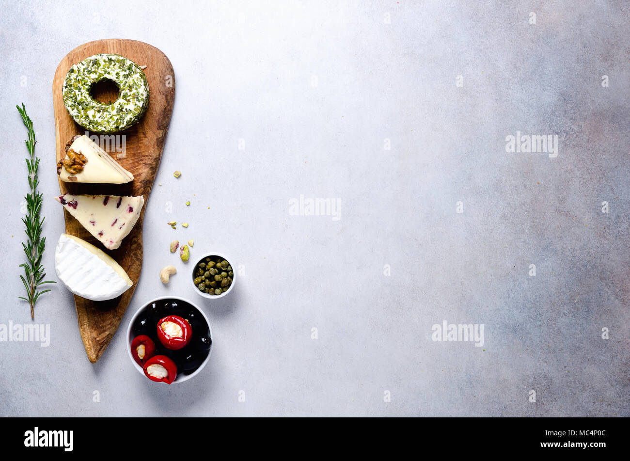 Assortment of hard, semi-soft and soft cheeses with olives, grissini bread sticks, capers, grape, on grey concrete backgound. Top view, copy space, flat lay. Cheese selection appetizer plate. - Stock Image