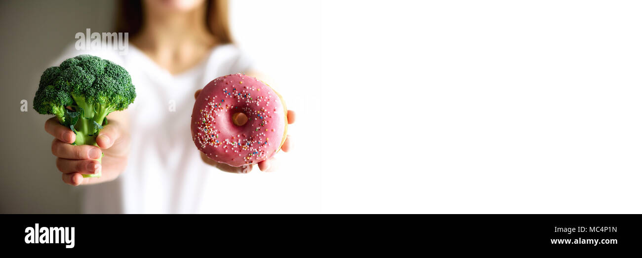 Young woman in white T-shirt choosing between broccoli or junk food, donut. Healthy clean detox eating concept. Vegetarian, vegan, raw concept. Copy space. Banner - Stock Image
