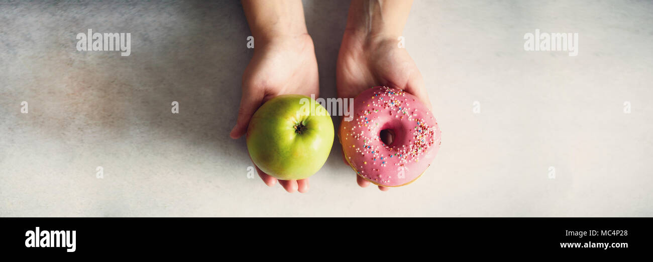 Young woman in white T-shirt choosing between green apple or junk food, donut. Healthy clean detox eating concept. Vegetarian, vegan, raw concept. Copy space. Banner - Stock Image