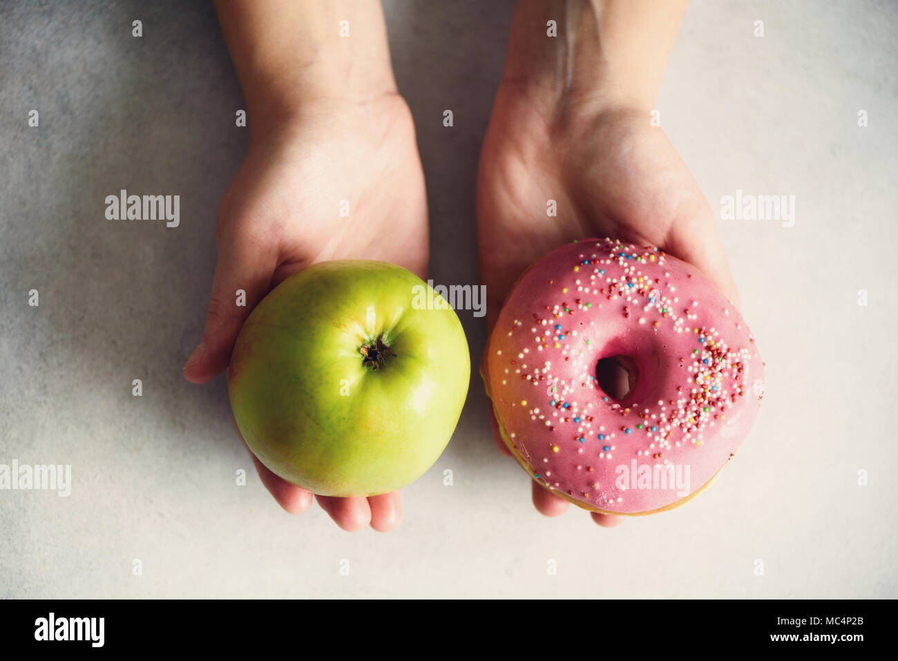Young woman in white T-shirt choosing between green apple or junk food, donut. Healthy clean detox eating concept. Vegetarian, vegan, raw concept. Copy space - Stock Photo