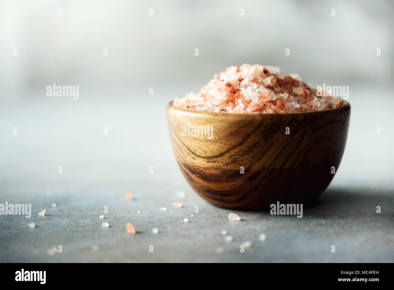 Pink Himalayan salt crystals and powder in wooden bowls on grey concrete background. Healthy diet without salt. Copy space - Stock Image