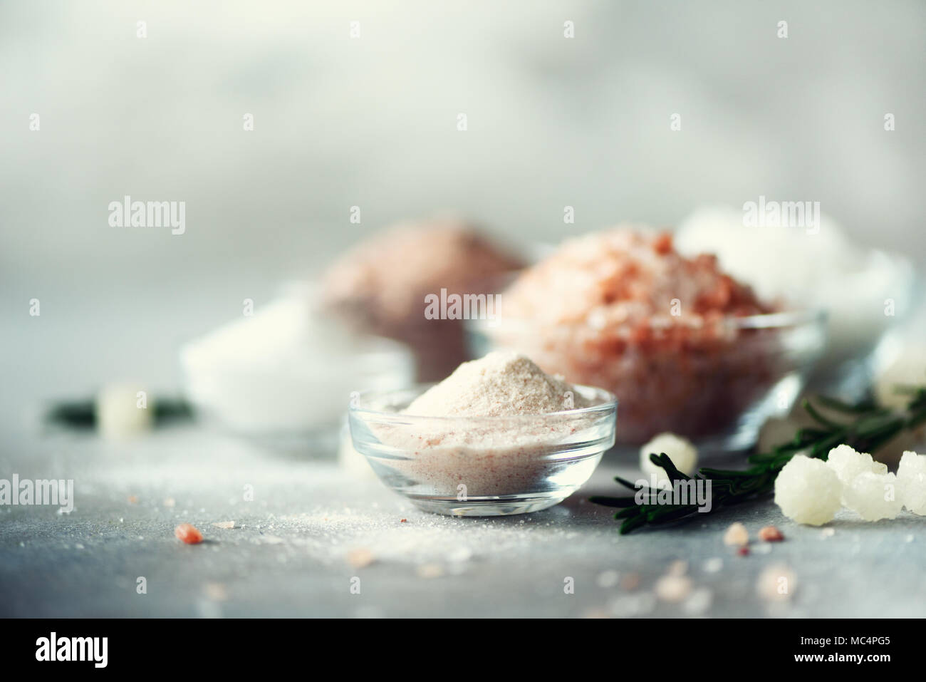 Mix of different salt types on grey concrete background. Sea salts, black and pink Himalayan salt crystals, powder, rosemary. Salt crystal balls from Dead sea. Copy space - Stock Image