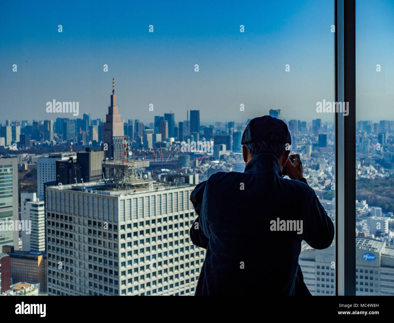 Tokyo Tourism Japan Tourism  - a tourist takes a photo from the viewing gallery of the Tokyo Metropolitan Government Towers in Tokyo Japan - Stock Image