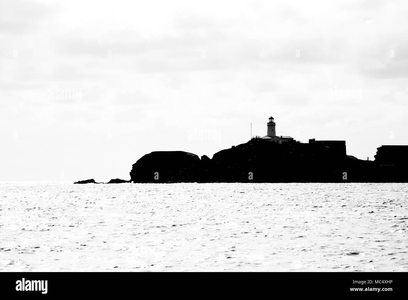 Black and white photography taken from the sea of a small island with a lighthouse at the top of the Hyères Islands archipelago Stock Photo