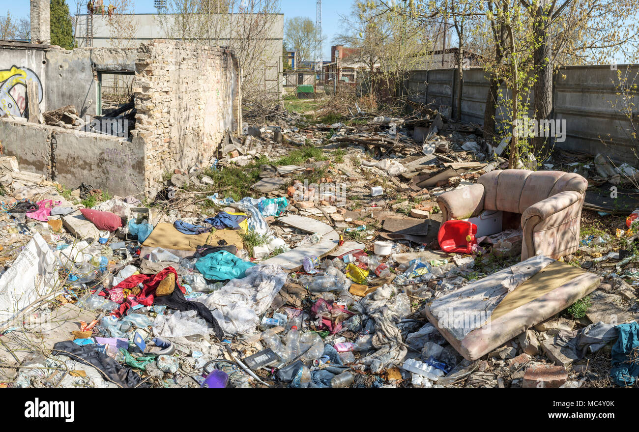 Old sofa at  a junkyard full of litter. - Stock Image