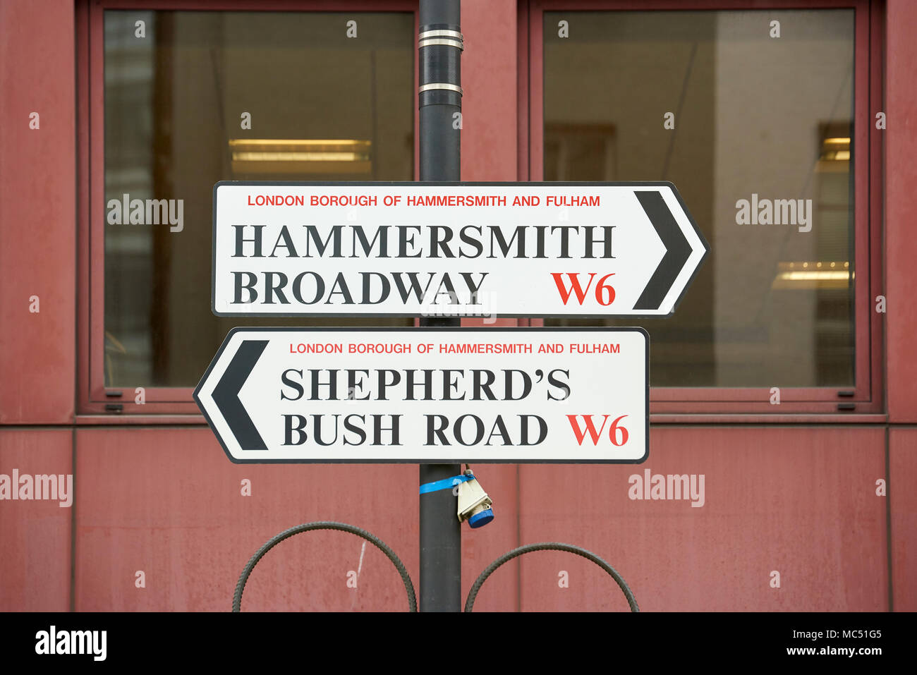 Street sign with directions to Hammersmith and Shepherds Bush, both located within the London Borough of Hammersmith and Fulham. Stock Photo