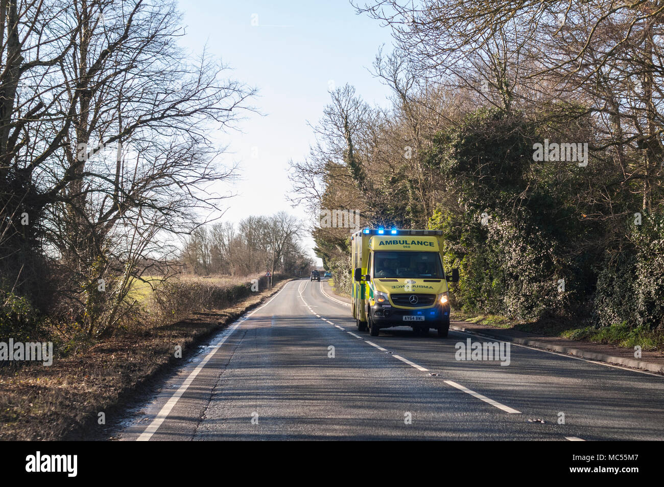 An ambulance with blue lights flashing on a main road in Norfolk , England , Uk - Stock Image