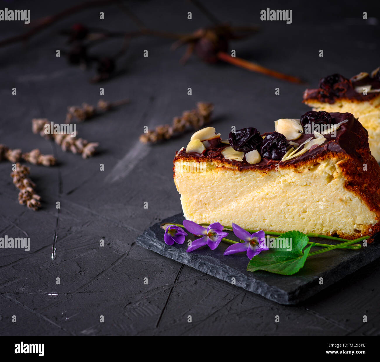 piece of cheesecake poured with chocolate and almond shavings on a black background, empty  space - Stock Image