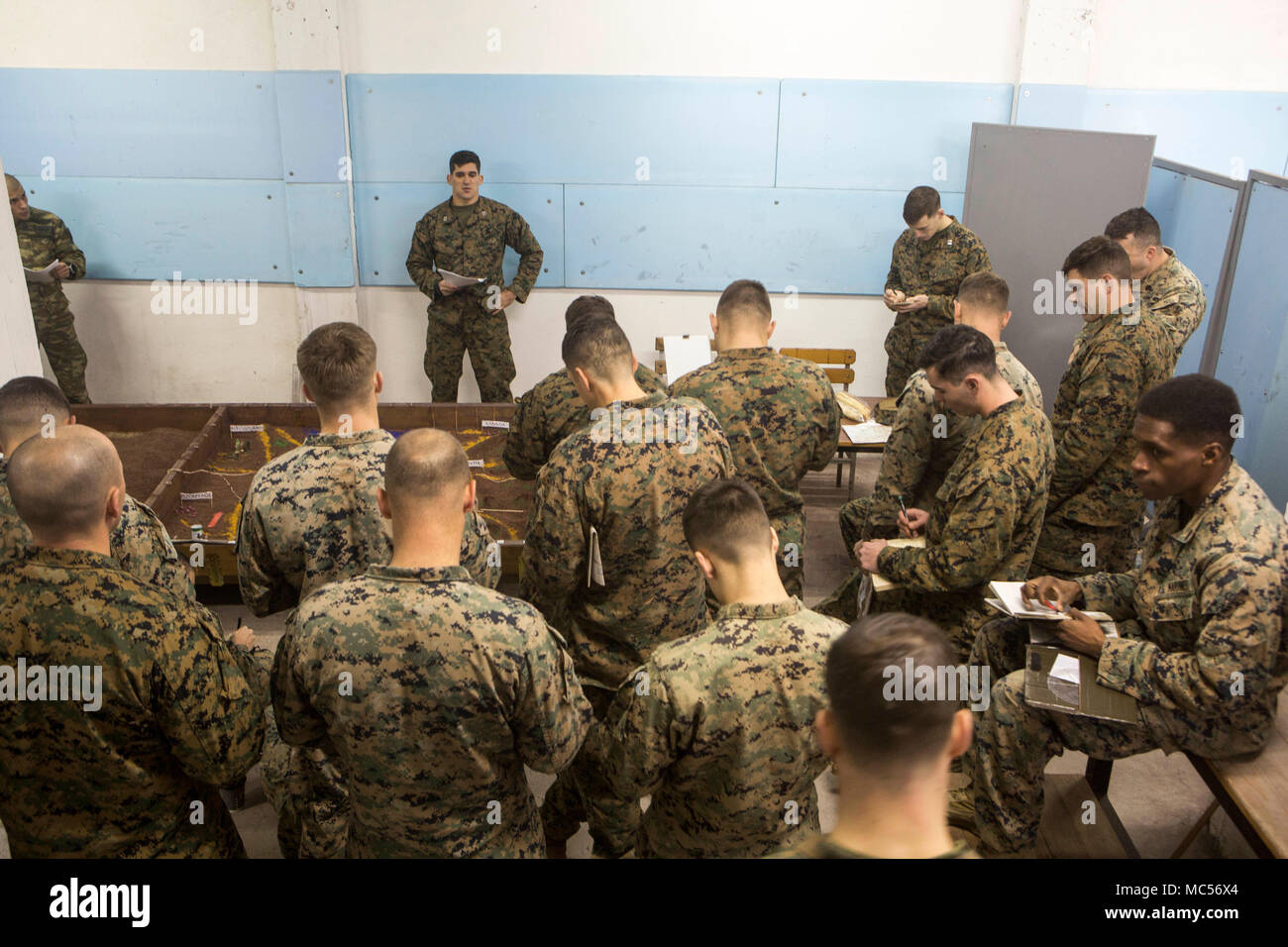 U.S. Marines with Black Sea Rotational Force 17.2 and Greek Marines with 32nd Marine Brigade use a terrain model to plan for a force-on-force attack in Volos, Greece Jan. 16, 2018. During the exercise Alpha and Bravo companies will conduct combined company-level tactical operations to seize the battalion objective. Stock Photo