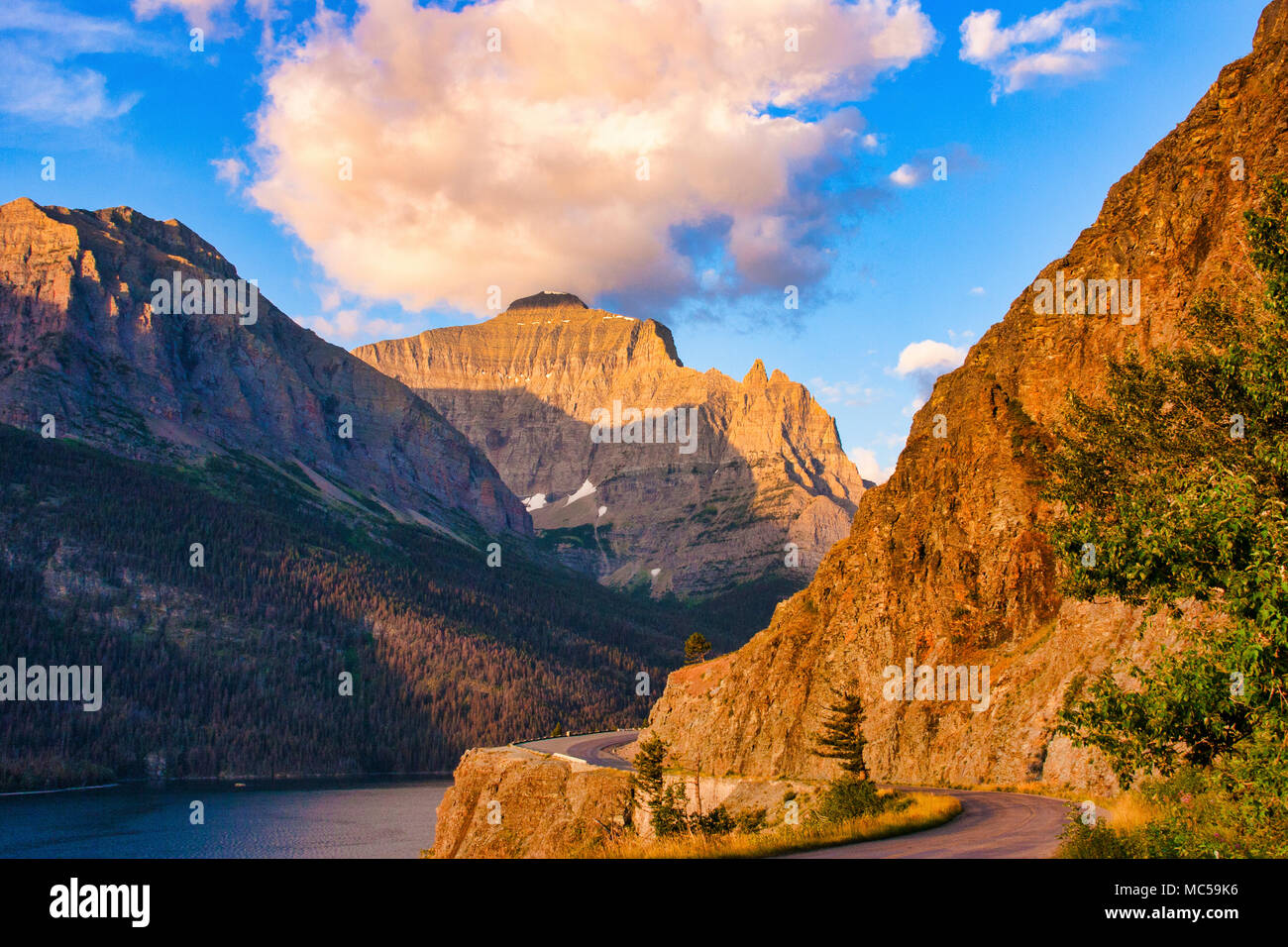 Sunrise lighting the mountains along Going to the Sun Road in Glacier National Park in Montana. - Stock Image