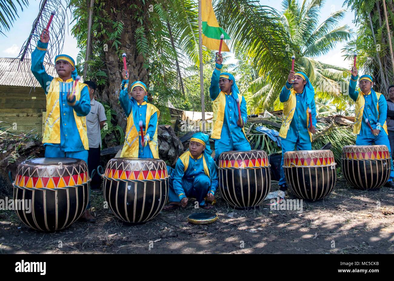 180402-N-RM689-0456  BENGKULU, Indonesia (April 2, 2018) Indonesians play the traditional bongos during a groundbreaking ceremony for the Peletakan Batu Partama Pembangunan shelter during the Indonesia mission stop for Pacific Partnership 2018 (PP18). PP18's mission is to work collectively with host and partner nations to enhance regional interoperability and disaster response capabilities, increase stability and security in the region, and foster new and enduring friendships across the Indo-Pacific Region. Pacific Partnership, now in its 13th iteration, is the largest annual multinational hum - Stock Image