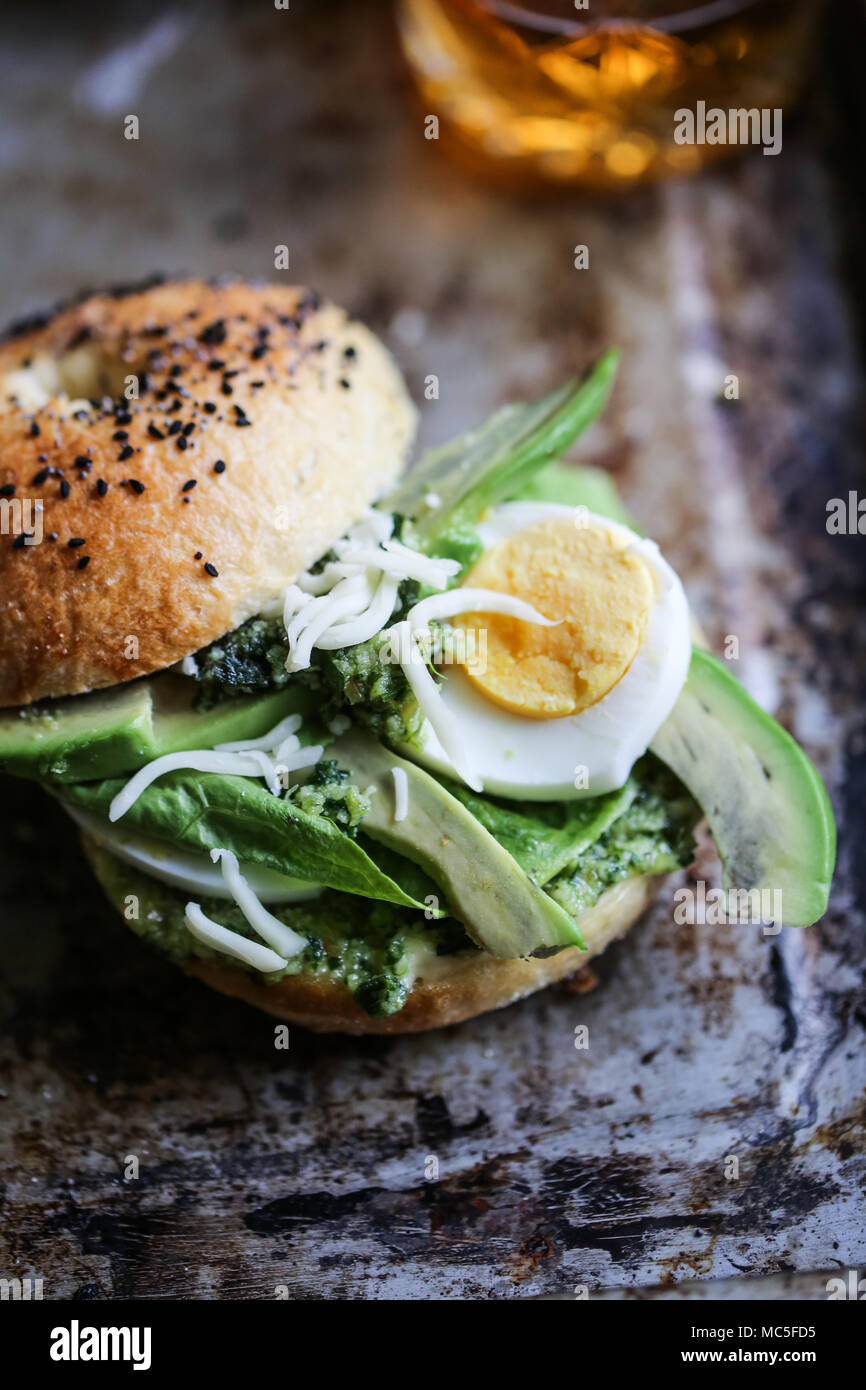 Green goddess bagel sandwich with avocado and hard boiled egg - Stock Image