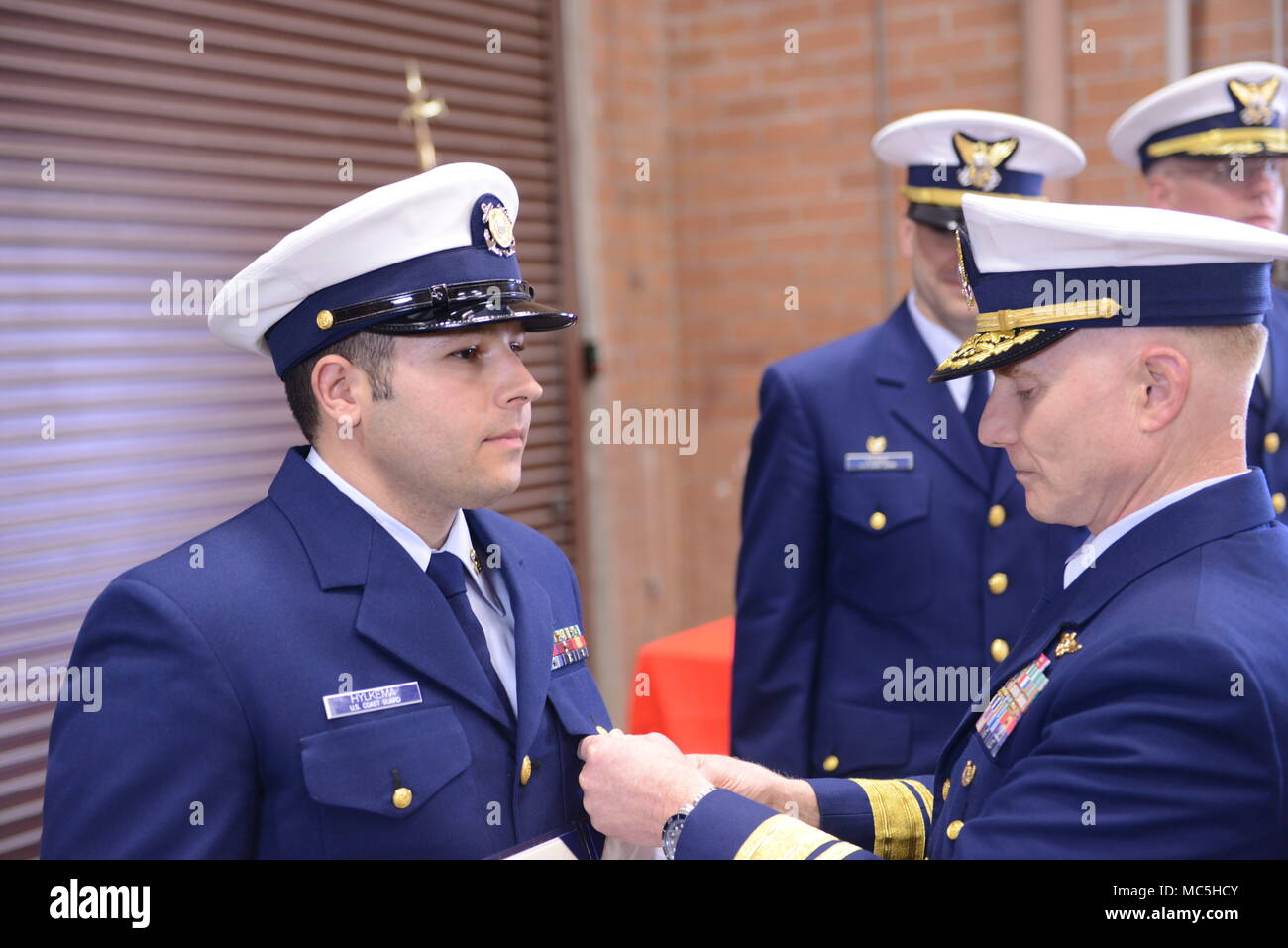 Rear Adm. David Throop, commander Coast Guard 13th District, clips the Coast Guard Medal onto Petty Officer 1st Class Jacob Hylkema, a boatswain's mate at Coast Guard Station Grays Harbor, during a ceremony held at the station's base in Westport, Wash., April 6, 2018.    The Coast Guard Medal is the 3rd highest award that a Coast Guardsman can be awarded during peacetime.    U.S. Coast Guard photo by Petty Officer 1st Class Levi Read. - Stock Image