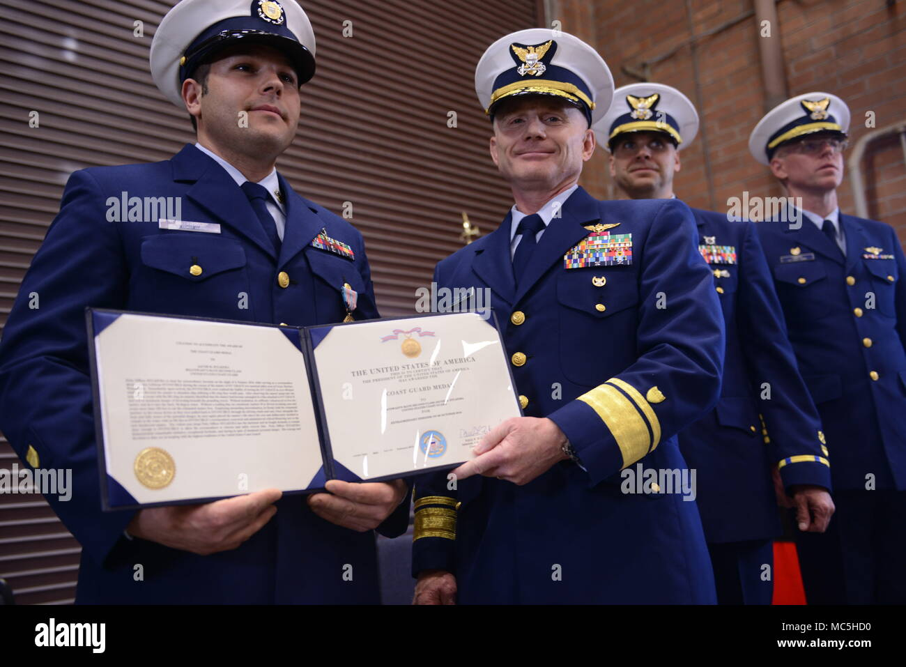 Rear Adm. David Throop, commander Coast Guard 13th District, presents the Coast Guard Medal to Petty Officer 1st Class Jacob Hylkema, a boatswain's mate at Coast Guard Station Grays Harbor, during a ceremony held at the station's base in Westport, Wash., April 6, 2018.    The Coast Guard Medal is the 3rd highest award that a Coast Guardsman can be awarded during peacetime.    U.S. Coast Guard photo by Petty Officer 1st Class Levi Read. - Stock Image
