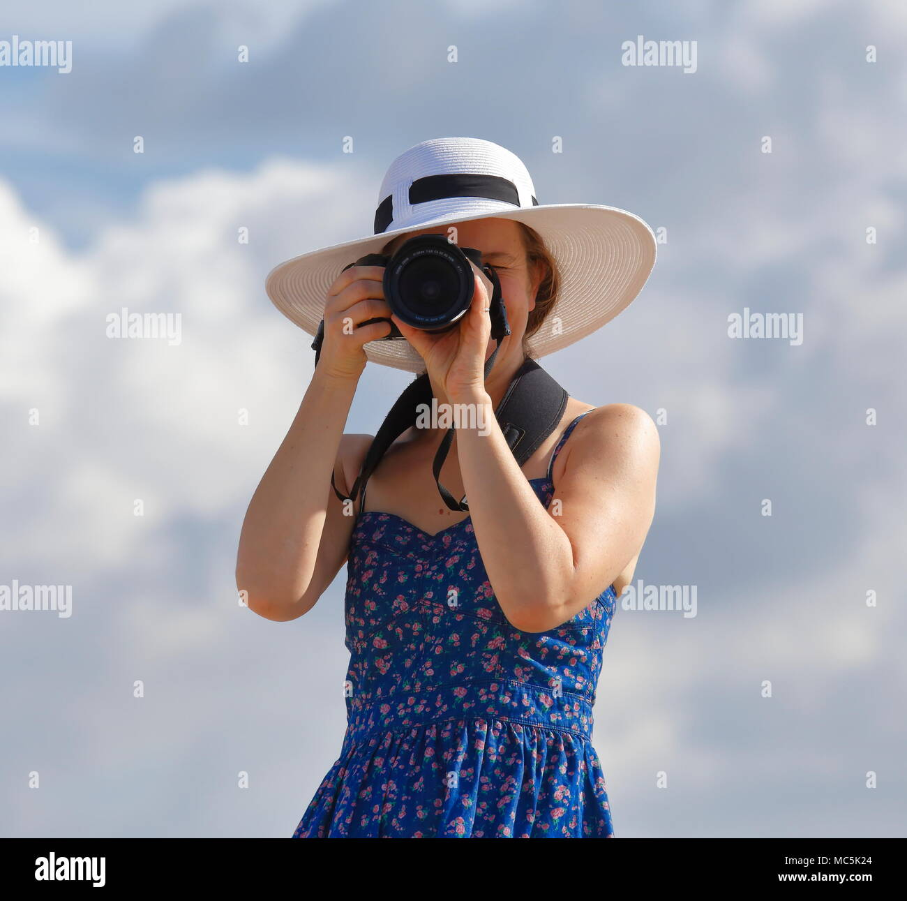 Young woman in white sunhat, sunglasses, and blue sundress. She is holding a camera to her eye and is looking straight towards the photographer - Stock Image