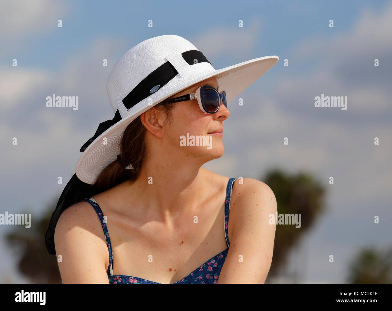 Profile view of a young woman in white sunhat, sunglasses, and blue sundress. Blurred trees, blue sky and clouds in the background - Stock Image