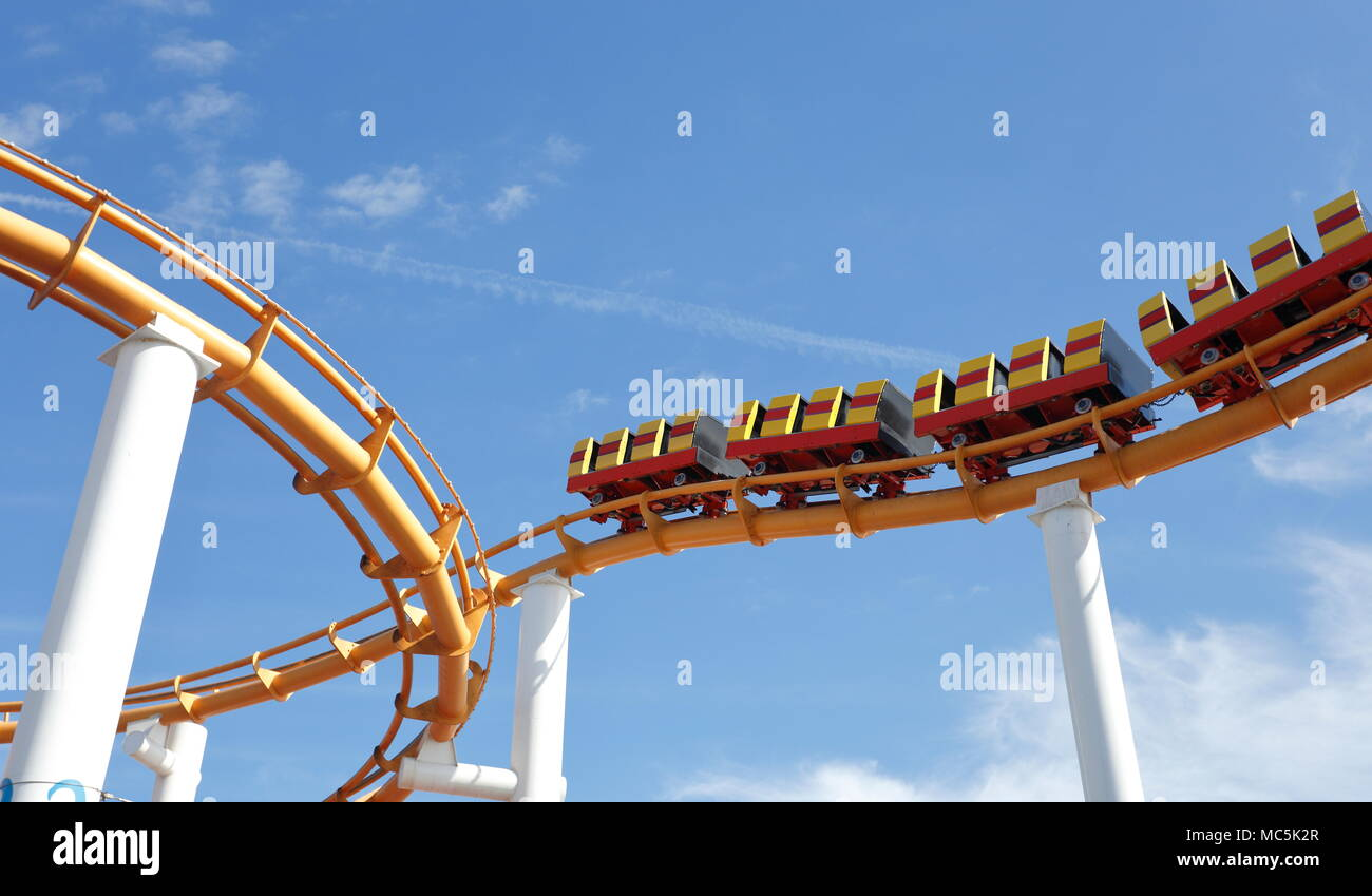 Abstract-style shot of the yellow roller-coaster at Pacific Park, Santa Monica against a blue sky with white clouds. No people visible in image - Stock Image