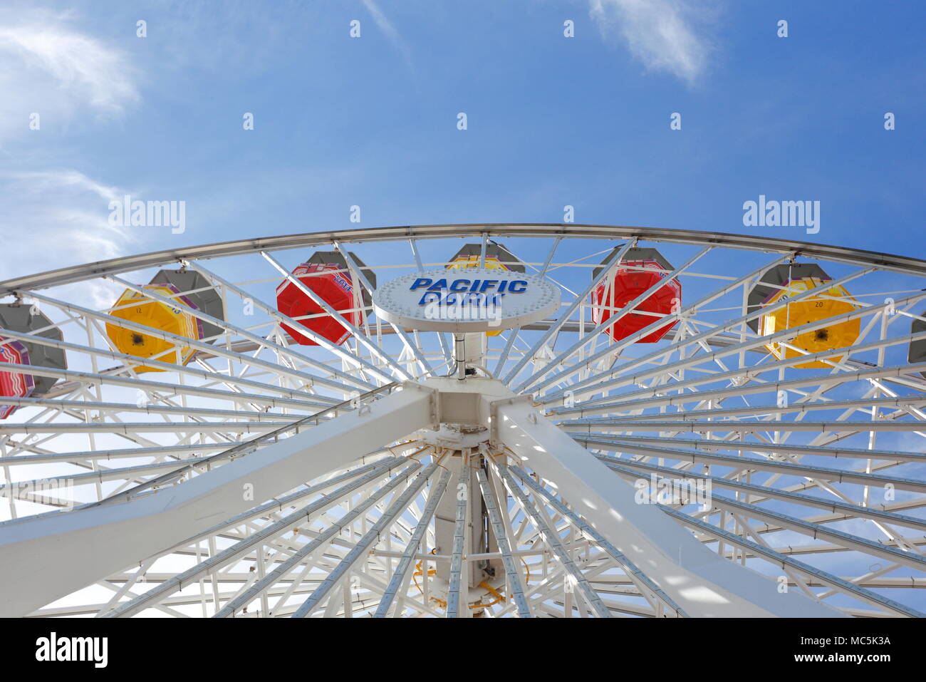 Ferris Wheel (Big Wheel) at Pacific Park, Santa Monica, California showing small segment of the wheel and gondolas (no people) against a blue sky - Stock Image