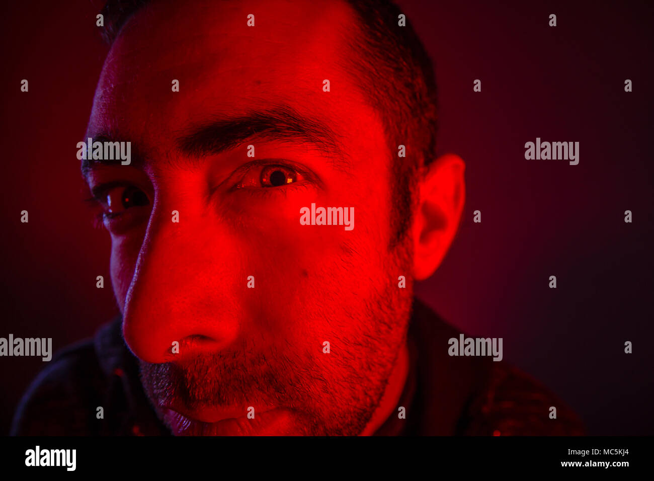 Man with suspicious facial expression. Close up portrait of doubt or skeptical young man. Also look like he is peeping. - Stock Image