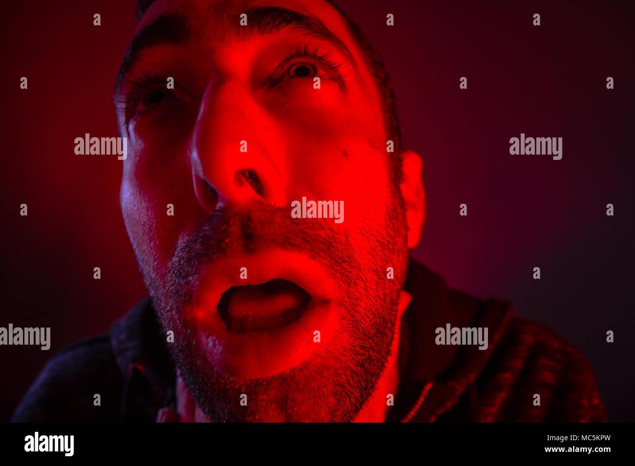 Depressed stressed man strangling himself. Close up headshot portrait of man chokes - Stock Image