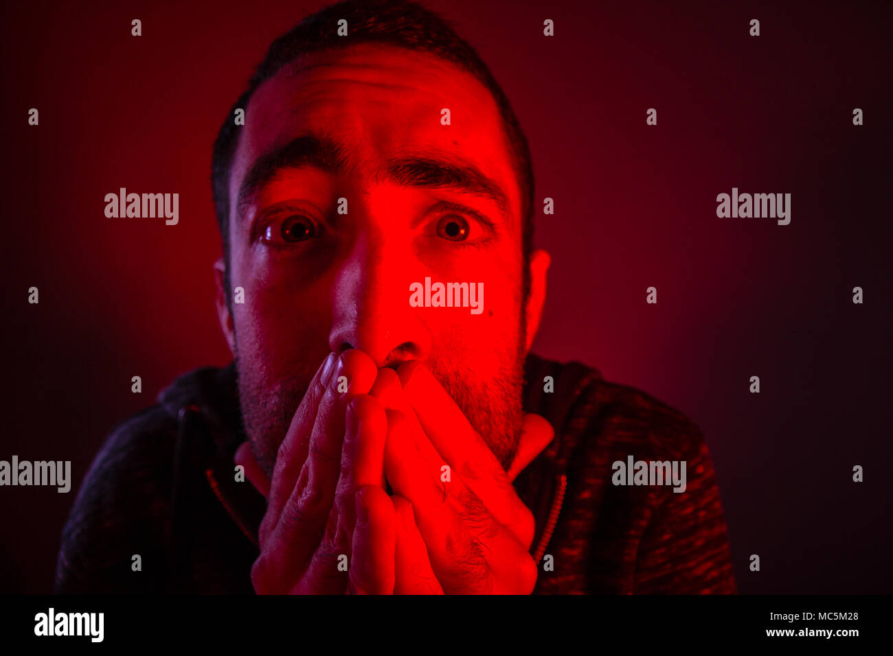 Stunned frightened man with surprised facial expression. Close up headshot portrait of shocked man with his hand on the face. - Stock Image