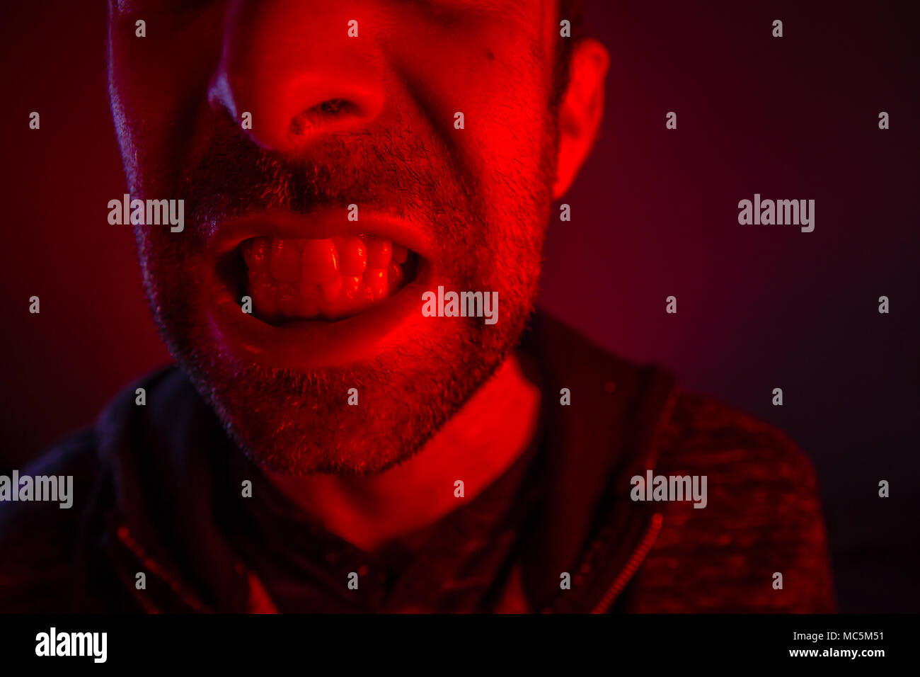 Man with angry facial expression. Close up portrait of a man with bared teeth. - Stock Image