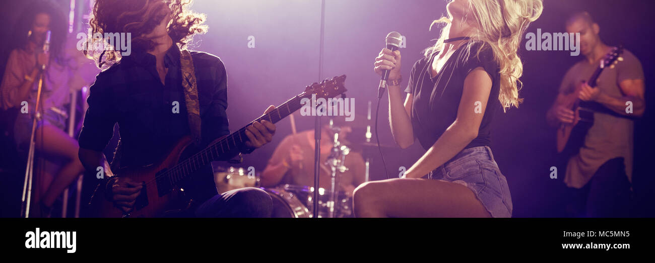 Singer and male guitarist with tousled hair performing at nightclub Stock Photo