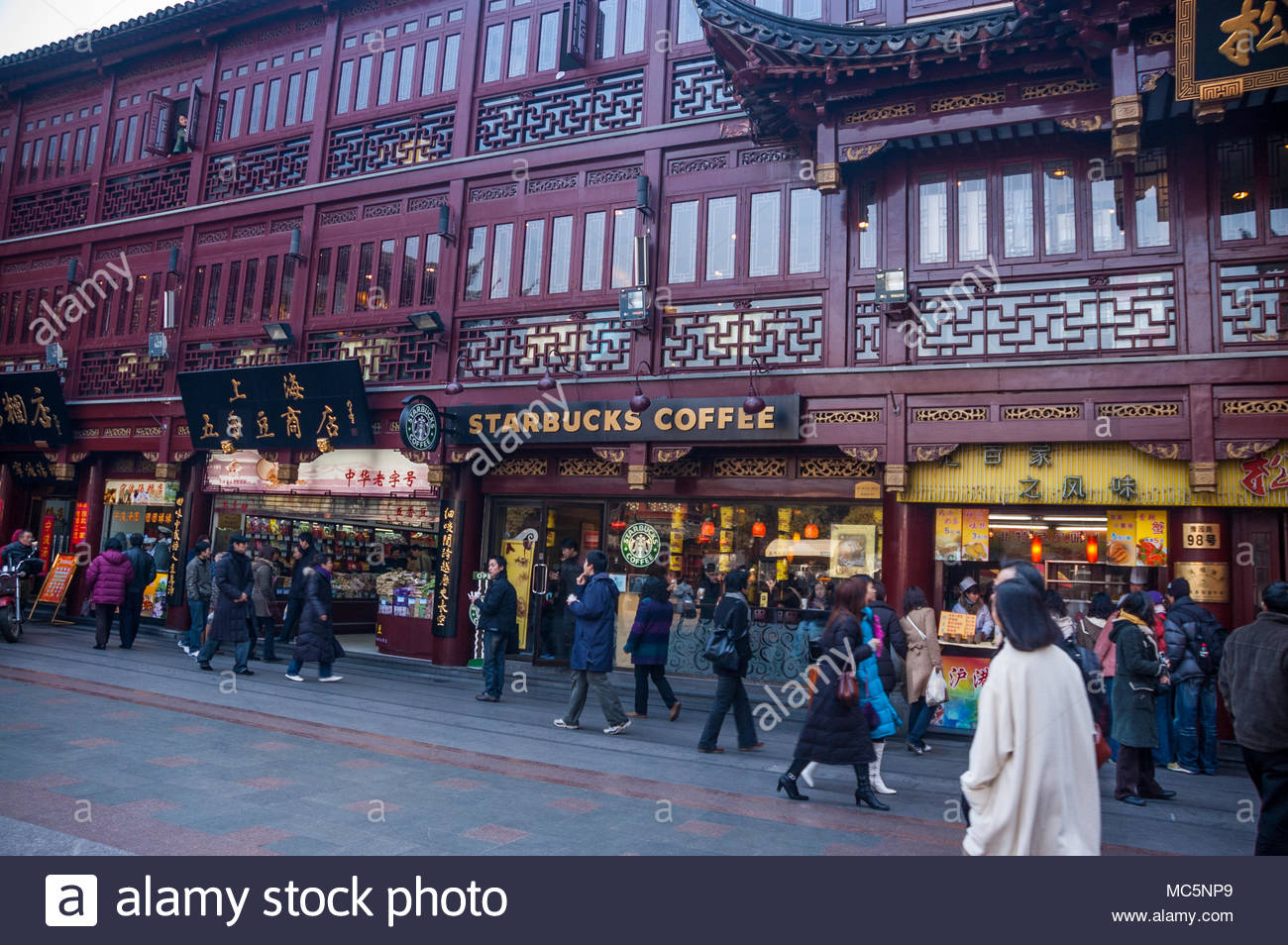 Tourists Pass A Starbucks Coffee Shop In A Traditional Looking