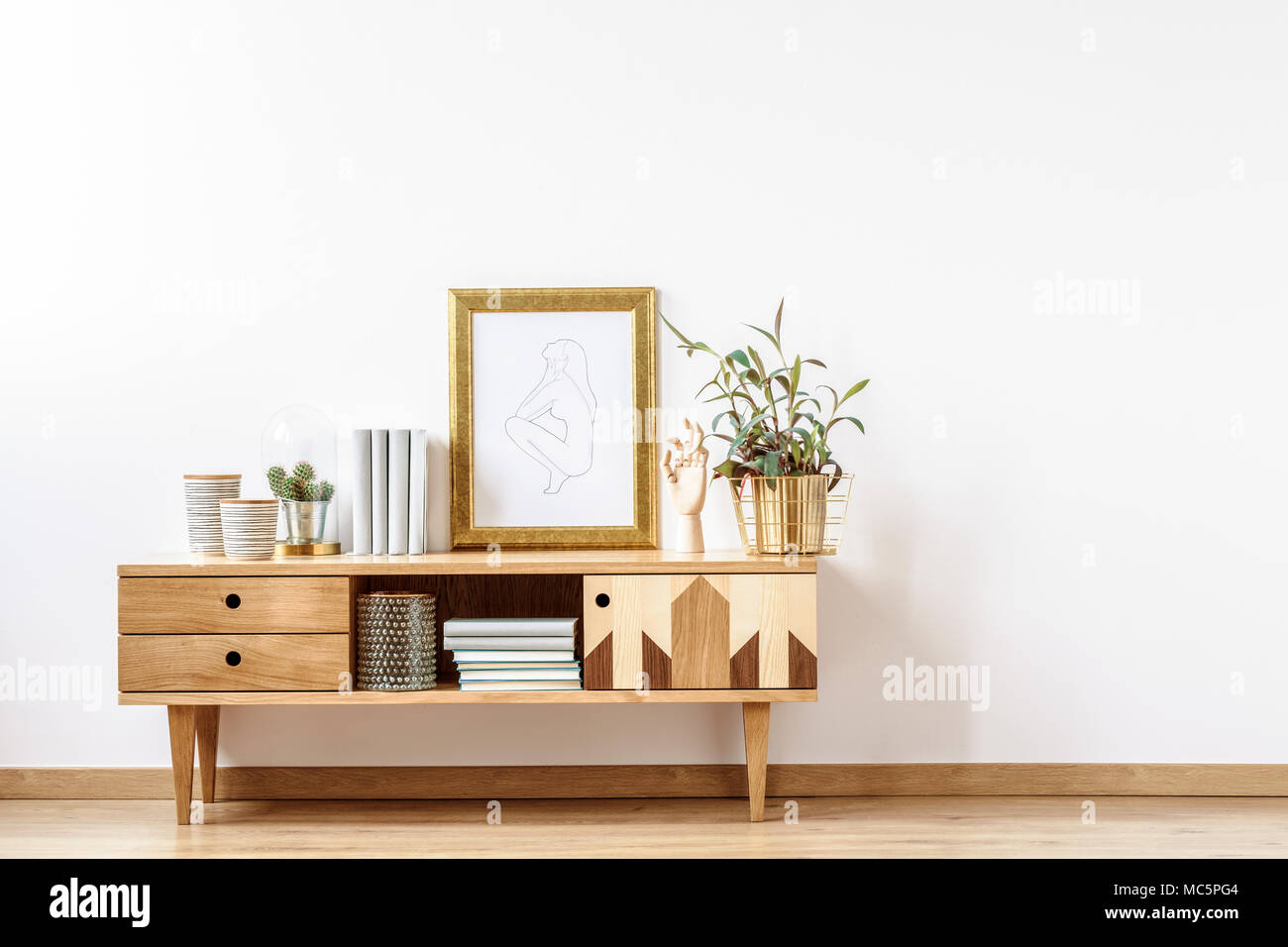 Scandinavian Wooden Cabinet With Books, Plants And Decorations By En Empty  Wall In A White